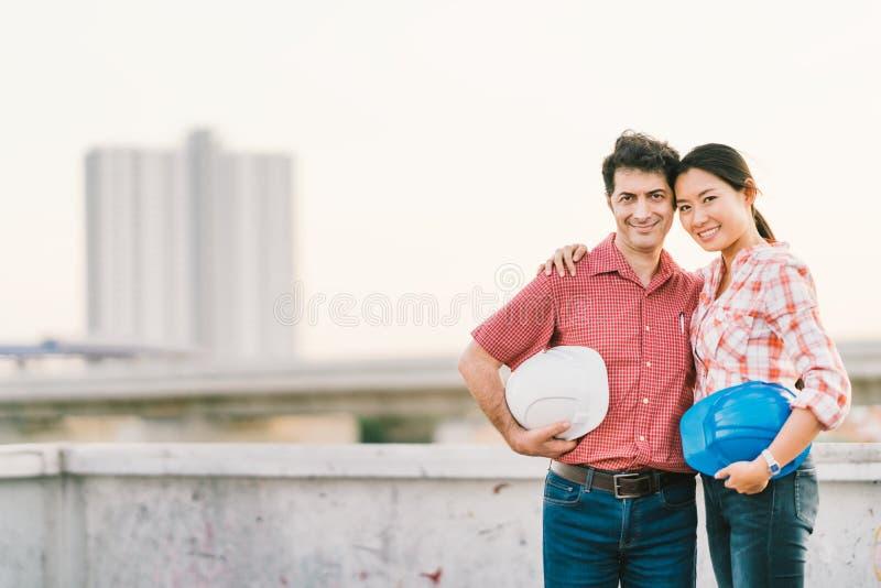 建筑工程师不同种族的夫妇建造场所或工厂的日落的,工业职业概念 免版税库存照片
