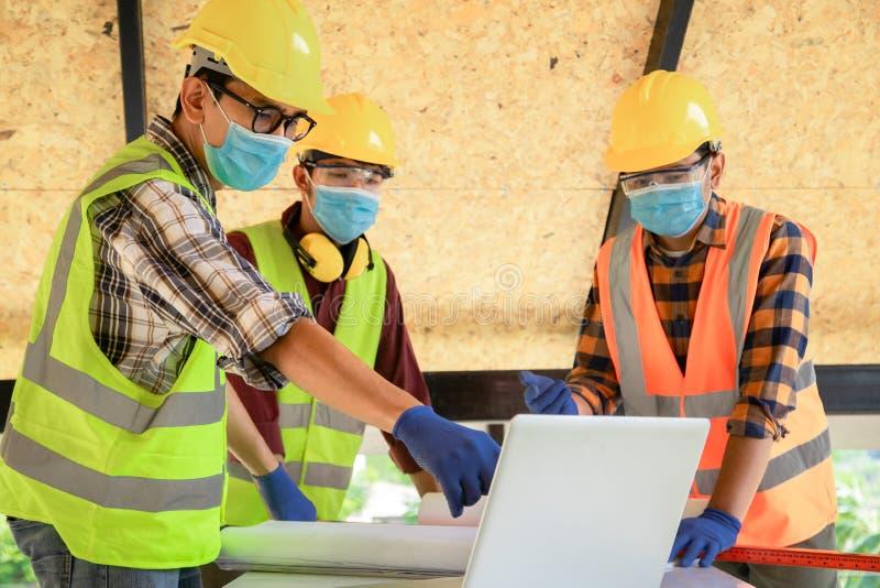 建筑工程师团队和三名建筑师准备戴医用口罩 冠状病毒或Covid-19在 库存照片