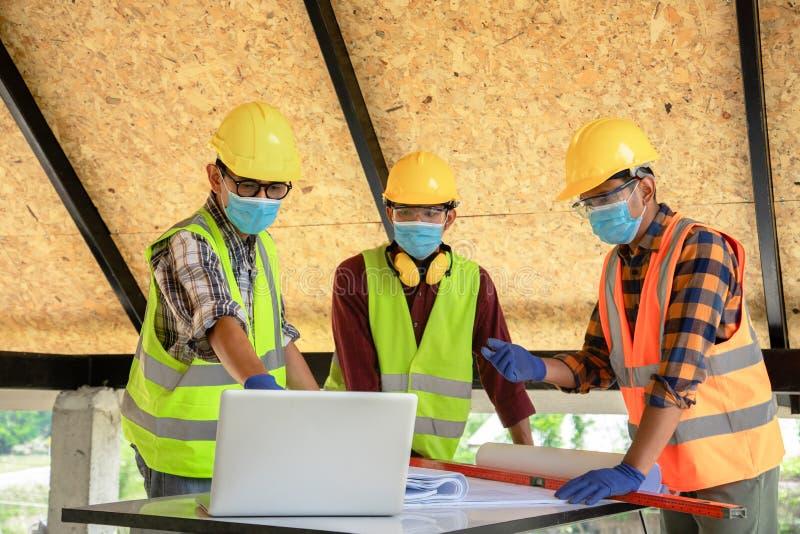 建筑工程师团队和三名建筑师准备戴医用口罩 冠状病毒或Covid-19在 免版税图库摄影