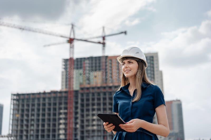 建筑工程师女性 有一台片剂计算机的建筑师在建造场所 少妇看,修造 库存图片