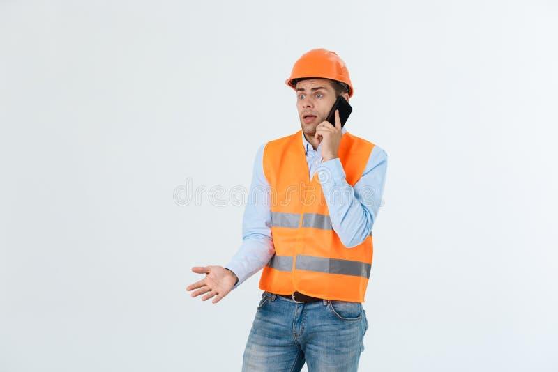 建筑工程师谈话在手机,使用智能手机的严肃的成年男性人为与工作者的通信 免版税库存照片