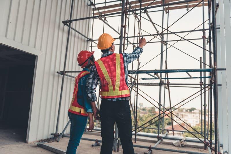 建筑工程师配合是检查站点修建和设施钢脚手架平台 项目负责人和 库存照片