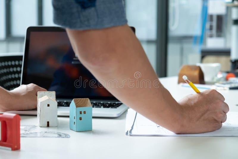 建筑师写着家庭计划并且使用膝上型计算机 免版税库存图片