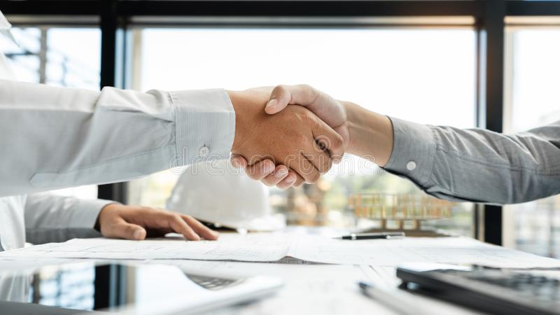 建筑师和工程师握手的建筑工人,当工作为配合和合作概念在的结束以后同意时 库存图片