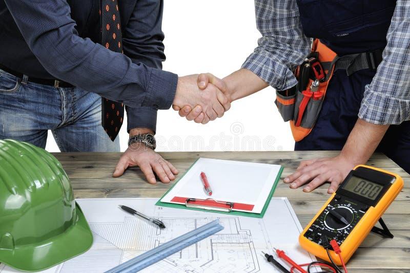 建筑师和年轻电工技术员握手在前面的 库存照片