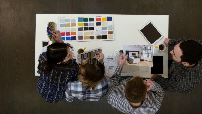 建筑师和设计师工作和多任务在办公室 免版税库存图片