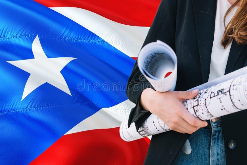 建筑师妇女反对波多黎各挥动的旗子背景的藏品图纸 建筑和建筑学概念 免版税库存照片