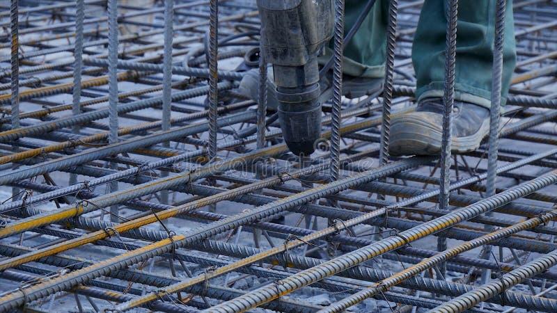 建筑查出的好成套装备工作者 工作者在做增强具体倾吐的建造场所金属框架 免版税库存照片