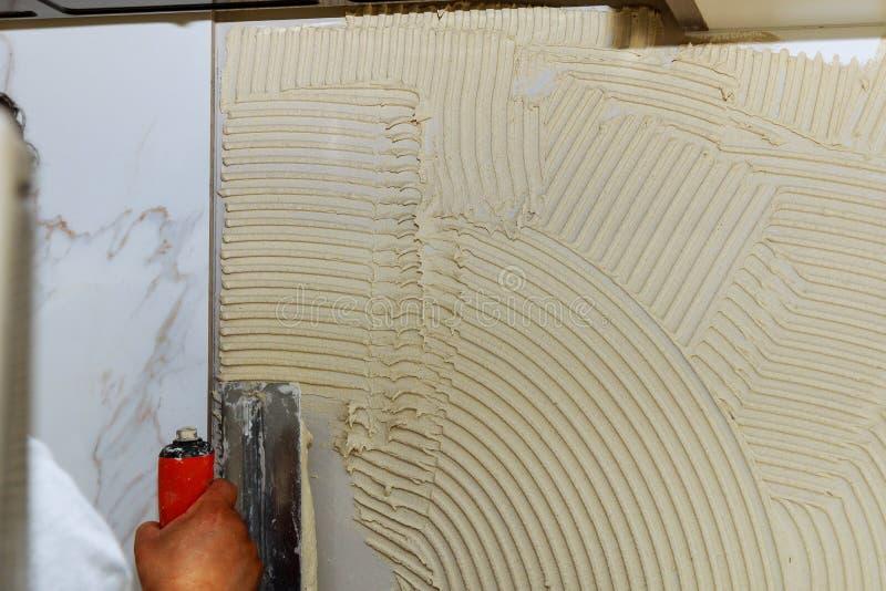 建筑泥工在瓦片的人手与水泥灰浆一起使用 免版税库存照片