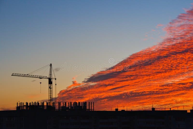 建筑用起重机和大厦剪影在日落天空背景与红色云彩 库存照片