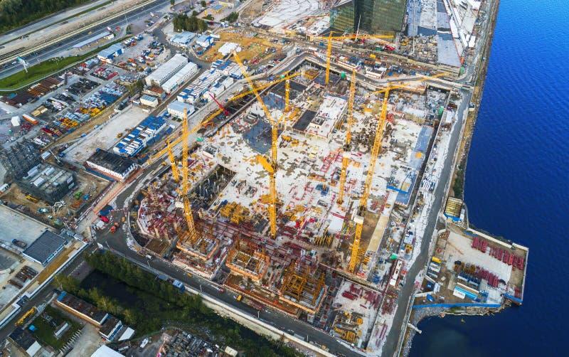 建筑用起重机塔的鸟瞰图 顶视图起重机和大厦工作进展 工作者 由寄生虫的建造场所视图 免版税库存照片