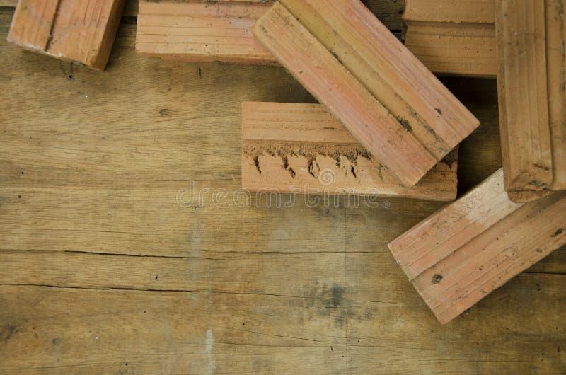 建筑的红砖在棕色木地板上 库存照片