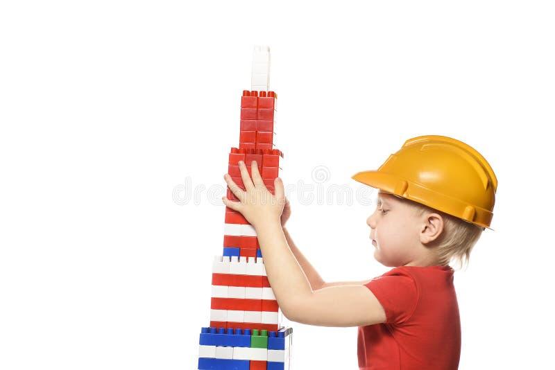 建筑盔甲和红色T恤杉的白肤金发的男孩修建从设计师的细节的一个摩天大楼 在空白背景的孤立 免版税库存图片