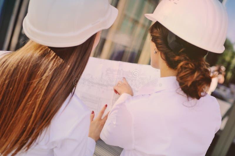 建筑盔甲的两位年轻俏丽的女商人工业工程师与一种片剂在手上在玻璃大厦 免版税库存图片