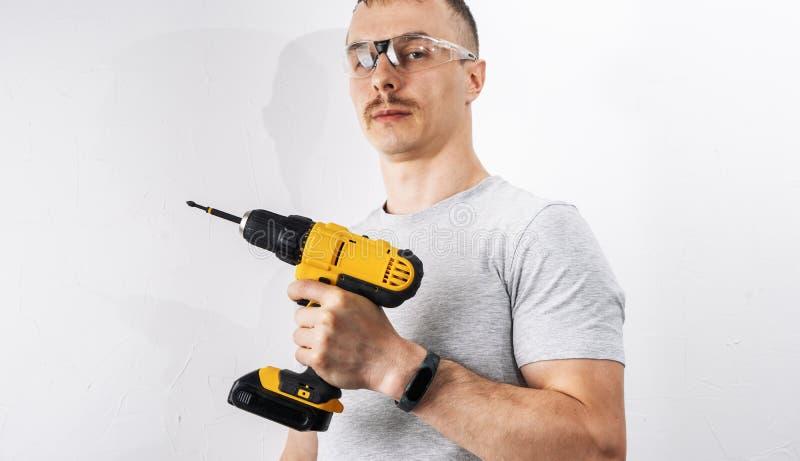建筑:防护玻璃的一个人拿着一把黄色电螺丝刀 图库摄影
