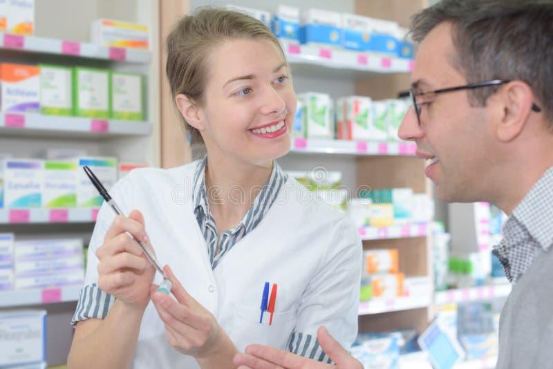 建议女性的药剂师关于药物用法的顾客在现代farmacy 免版税图库摄影
