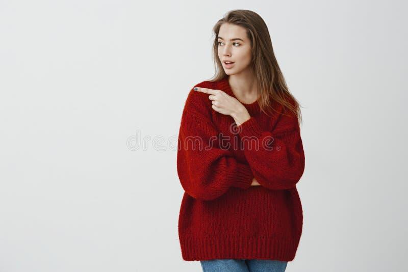 建议的女孩朋友击中在那个方向的酒吧 宽松红色毛线衣的被聚焦的严肃的可爱的妇女,看 库存照片