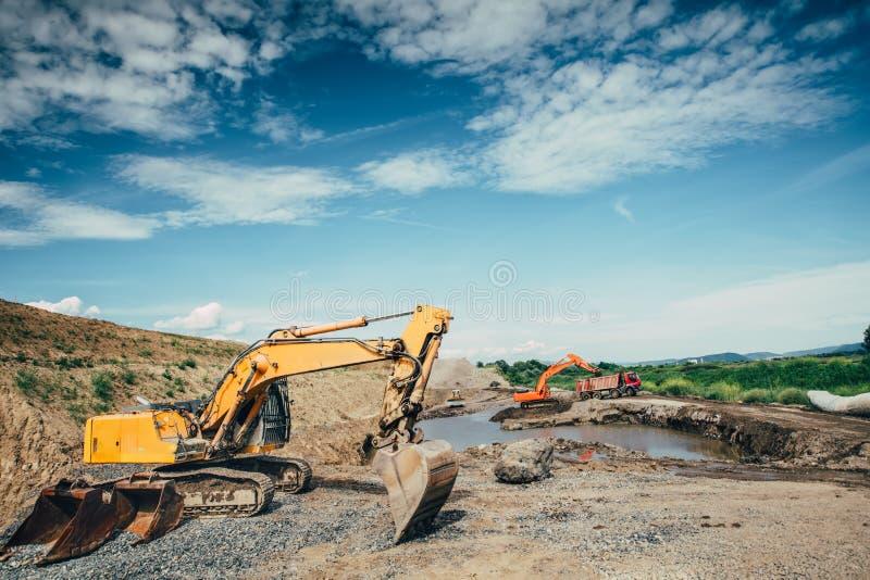建造场所与装载倾销者卡车、推土机、瓢工作和工程师的挖掘机的大厦细节 免版税库存照片