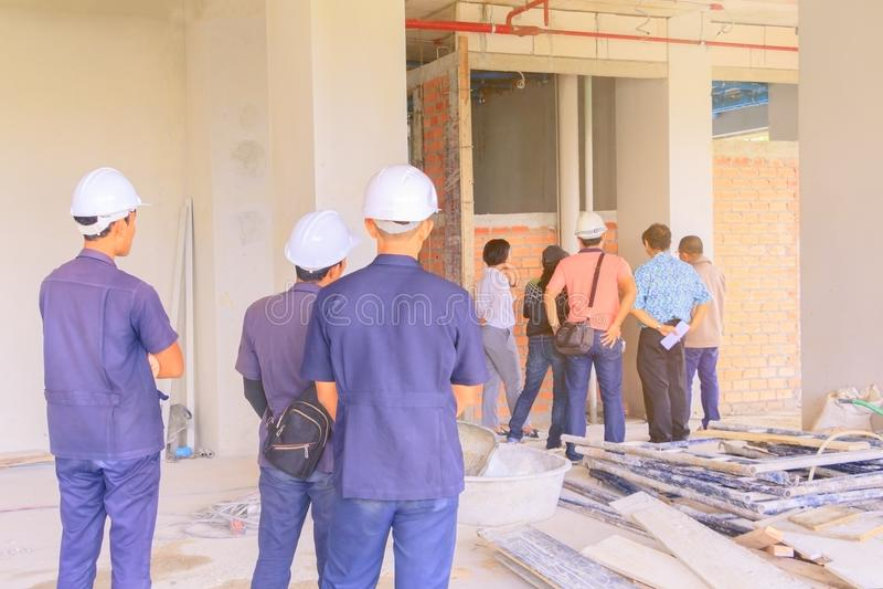 建造场所和工程师检查建立在安置高层建筑物的计划发展 库存照片