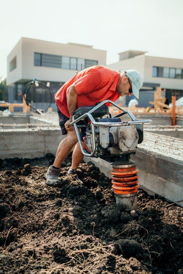 建造场所的工作者有变紧密的土壤的振动压路机的或土夯 库存图片