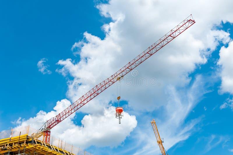 建造场所起重机举和有水泥的有同情心的桶在新的大厦或企业对象在有蓝天机智的城市 库存照片