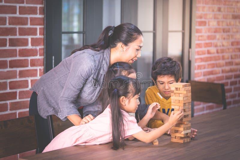 建造玩具与老师的孩子块塔 图库摄影