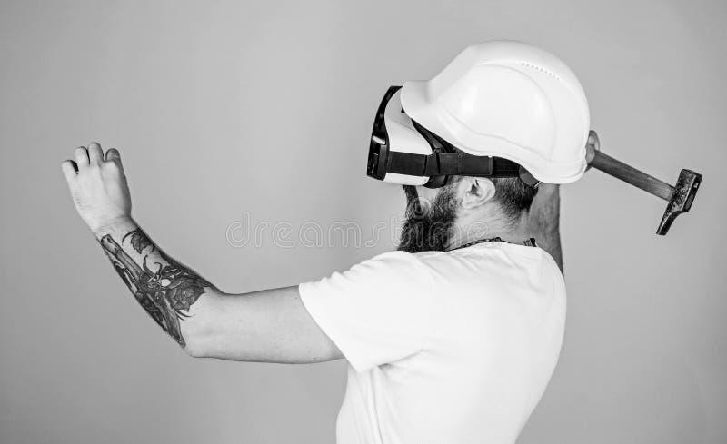 建造者和整修概念 行家繁忙与整修在虚拟现实中 有锤击真正钉子的HMD的人 免版税库存照片