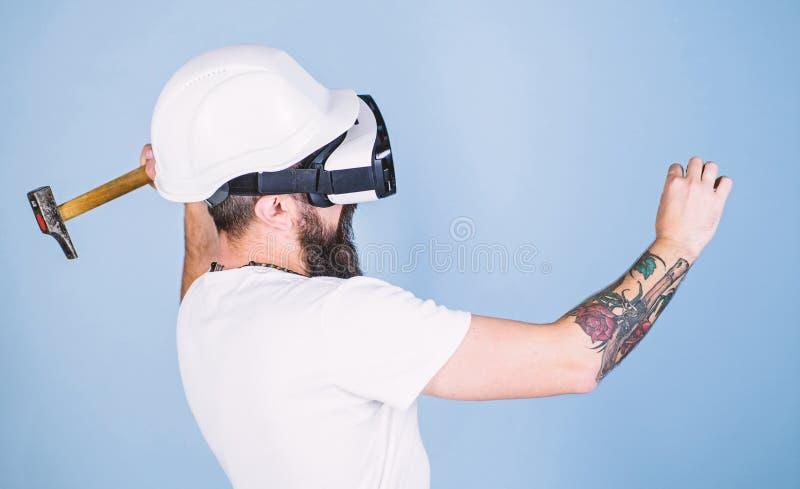 建造者和整修概念 行家繁忙与整修在虚拟现实中 有锤击真正钉子的HMD的人 库存图片
