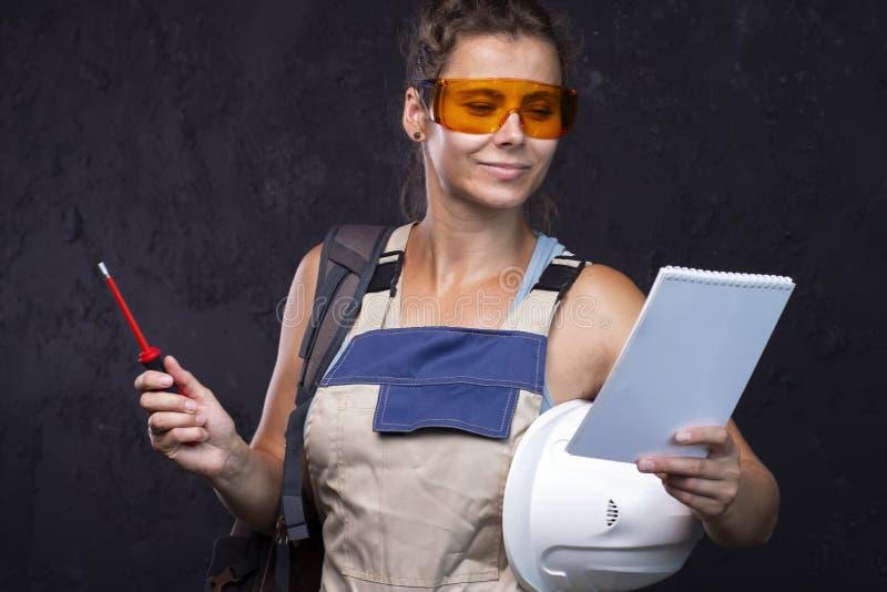 建造者妇女 制服的女工 放置户外站点的砖建筑 有清单的建筑师工程师 库存照片