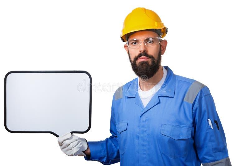 建造者工作者在拿着有copyspace的黄色盔甲的防护建筑白板,隔绝在白色背景 免版税库存图片