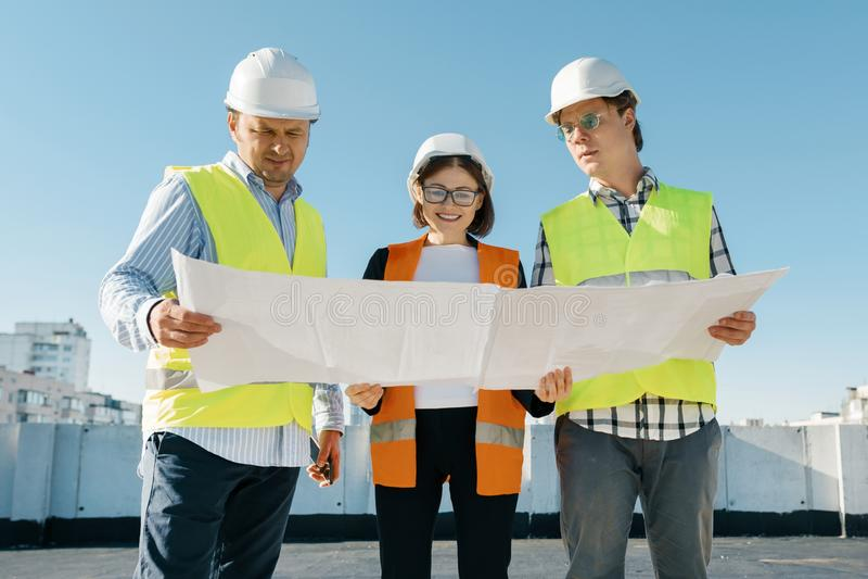 建造者工程师队工地工作的,读图纸 建筑、发展、配合和人概念 免版税库存图片