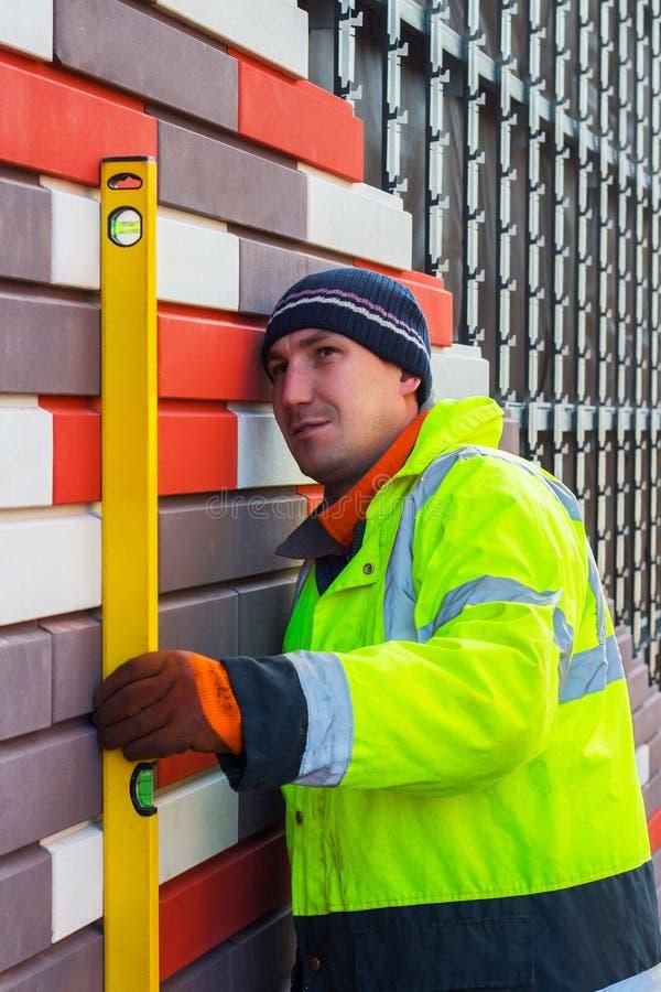 建造者检查被完成的工作的质量,保留水平面 免版税库存图片