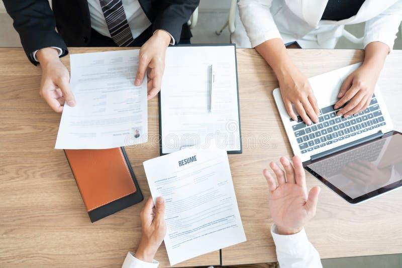 开一个业务会议读关于聘用的决定的严肃的人一份简历在面试中在公司中,可爱和 库存照片