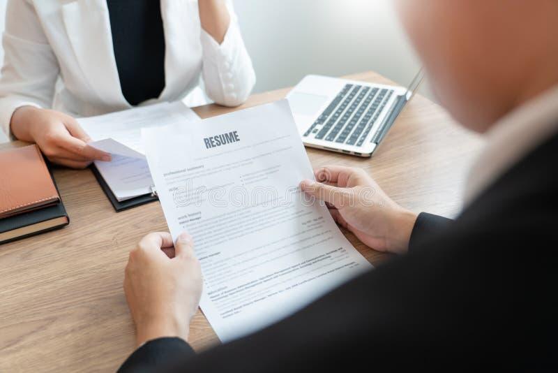 开一个业务会议读关于聘用的决定的严肃的人一份简历在面试中在公司中,可爱和 图库摄影