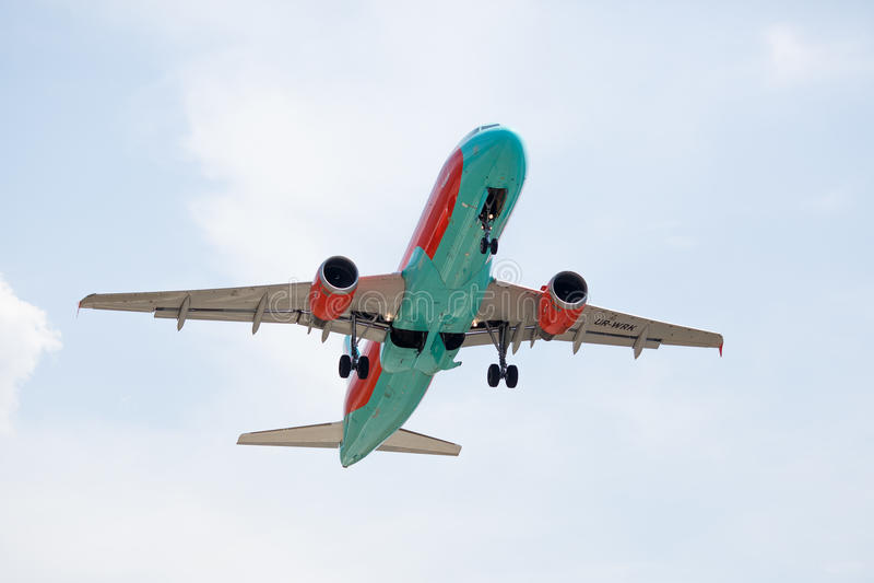 离开与在蓝天的云彩的飞机 免版税库存照片