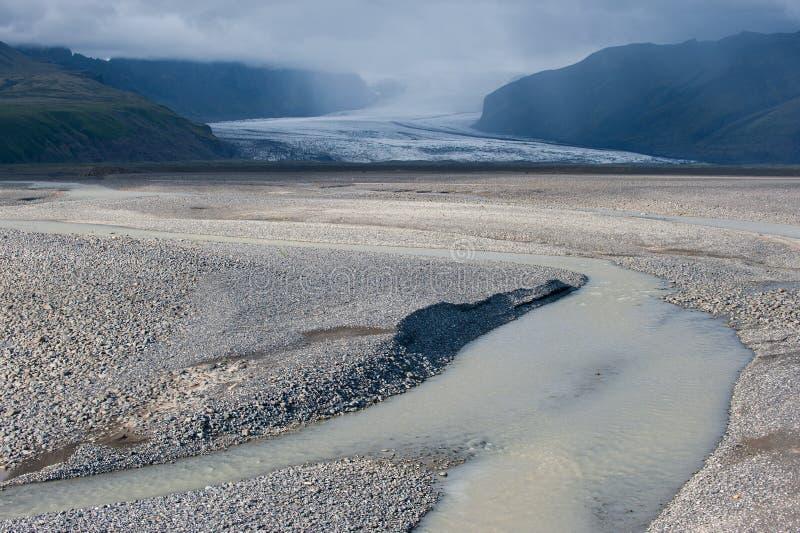 离开与河、冰川和风雨如磐的天空,冰岛的风景 免版税图库摄影