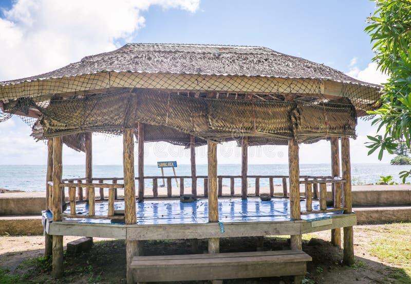 开侧边的海滩小屋或fale与被编织的棕榈叶屋顶由waterf 库存图片