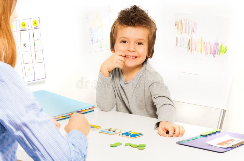 开发与卡片的微笑的男孩戏剧比赛 免版税库存照片
