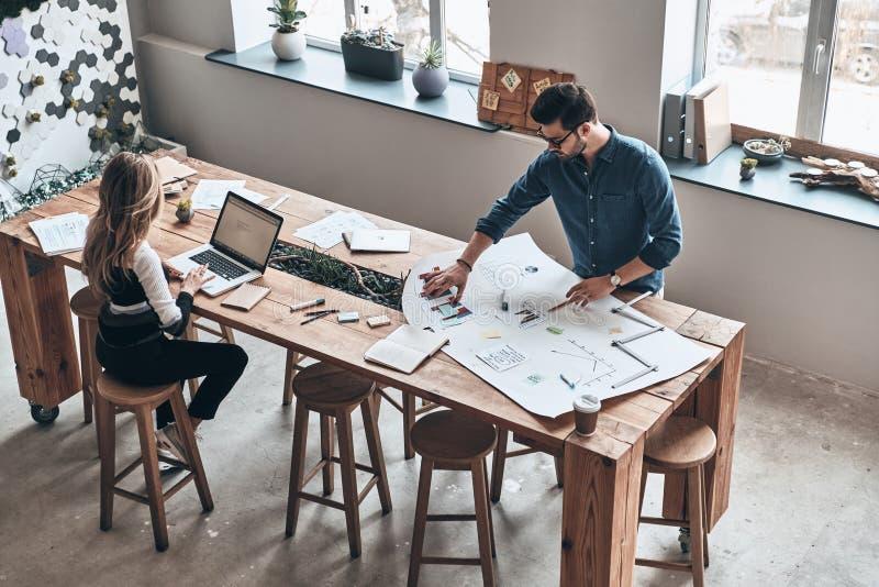 开发的新的战略 年轻同事顶视图聪明的便衣的使用图纸,当工作在创造性的运作的s时 免版税库存图片