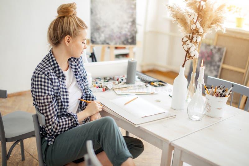 开发绘画的她自己的样式华美的逗人喜爱的白肤金发的女孩 免版税库存照片