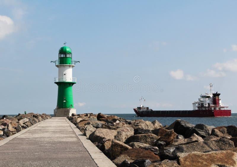 离开口岸的绿色和白色灯塔和货船 免版税库存照片