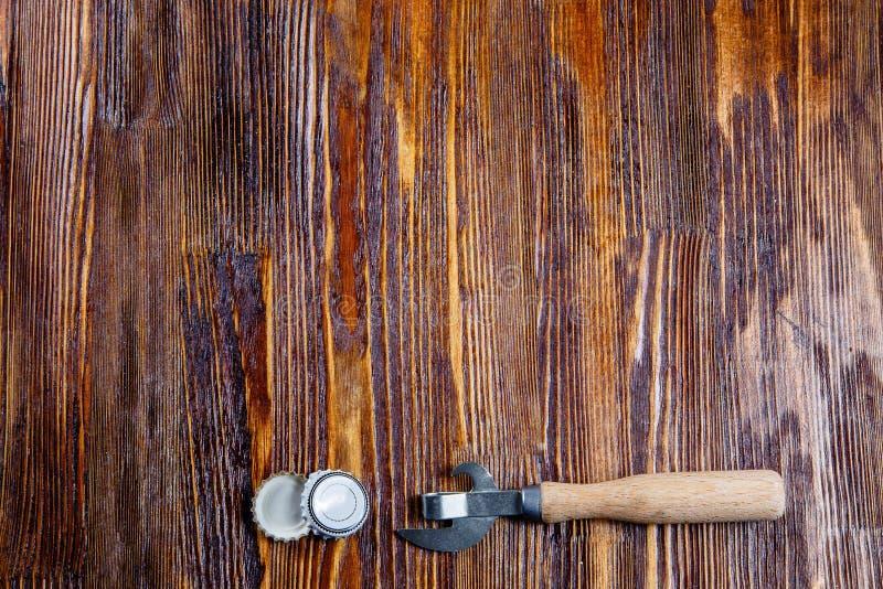 开启者和盒盖从啤酒在一张木桌上 框架 自由地方 免版税库存图片