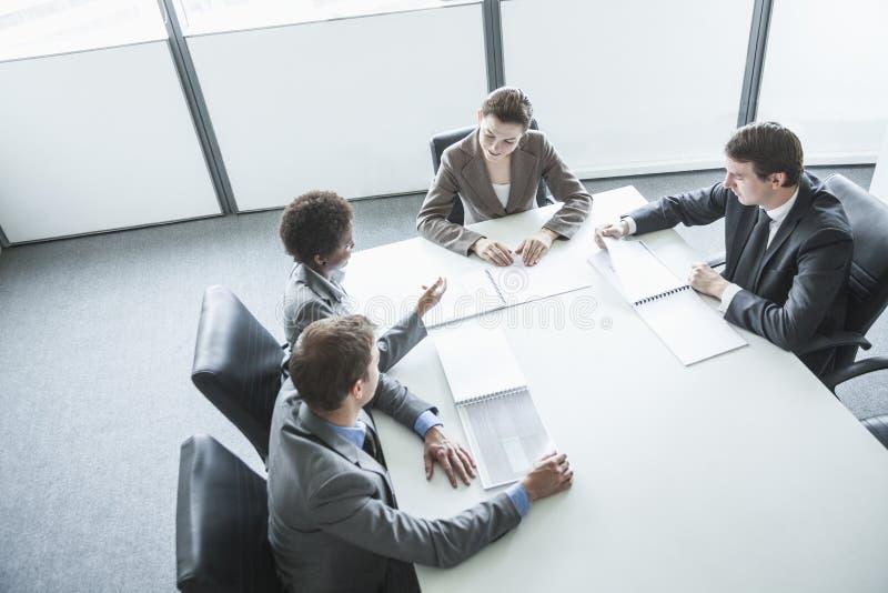 开四个的商人坐在桌附近和业务会议,大角度看法 免版税图库摄影