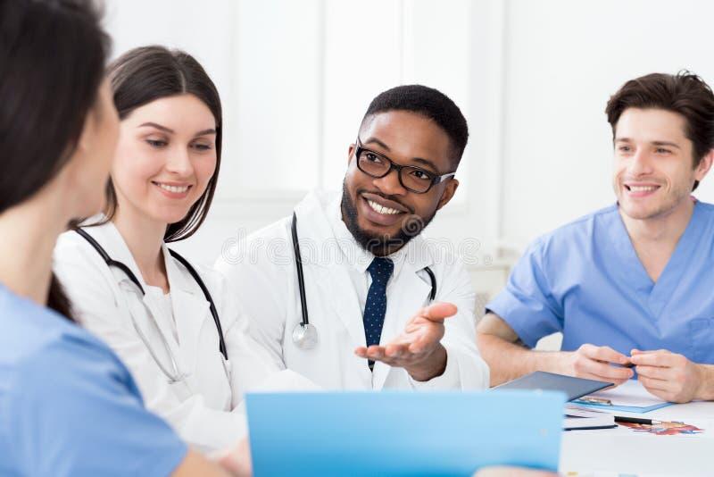 开多种族的医疗队会议,谈论患者纪录 图库摄影