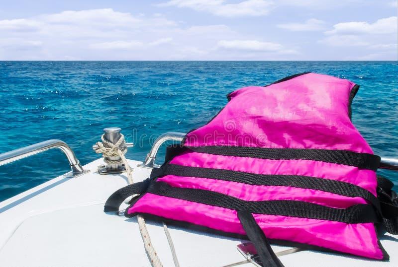 开始旅途到有安全速度小船概念、看法有移动与海景的救生背心的和天空的海与云彩在Backgro 免版税库存照片