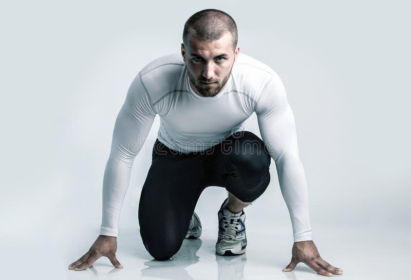 开始状态的可爱的运动员 隔绝在白色背景和在发光的地面 库存照片