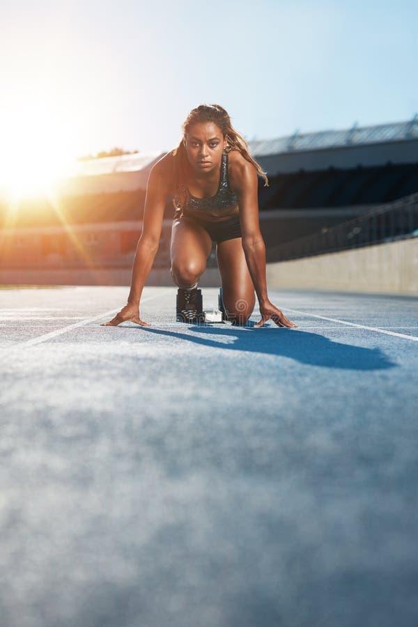 开始状态的年轻女性短跑选手在跑马场 图库摄影