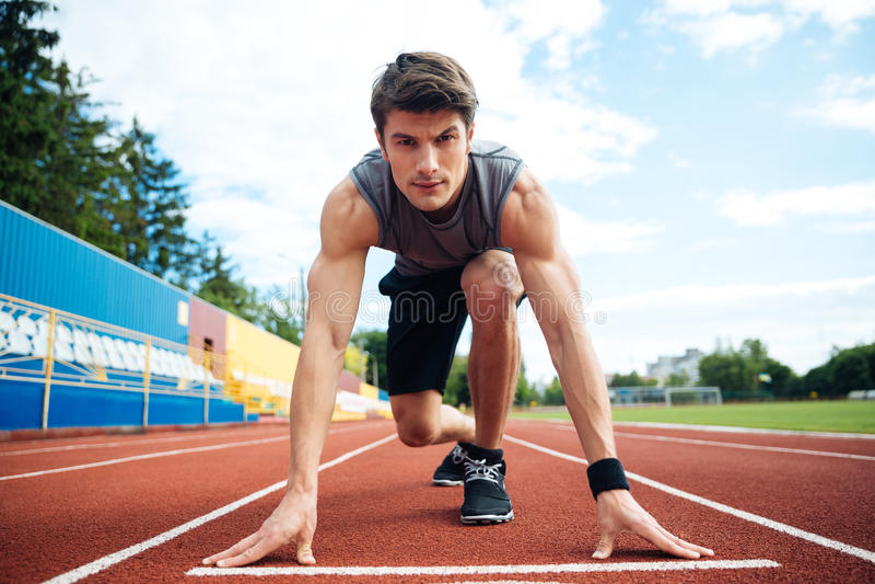 开始短跑的男性运动员看照相机 库存图片