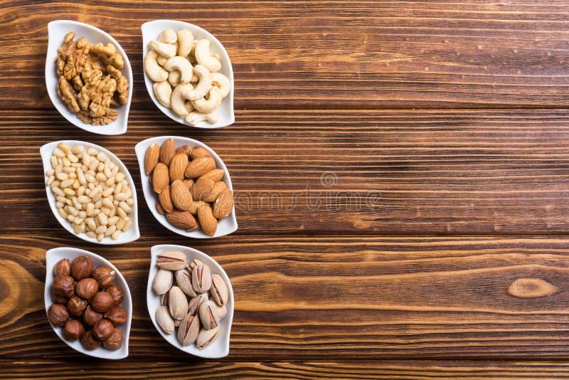 开心果、杏仁、核桃、松果、榛子和腰果 在碗backgrond的快餐 库存图片