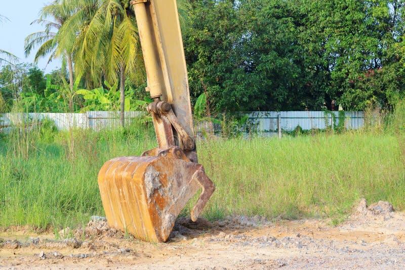 开掘与地板土壤的重的黄色挖掘机 免版税库存照片